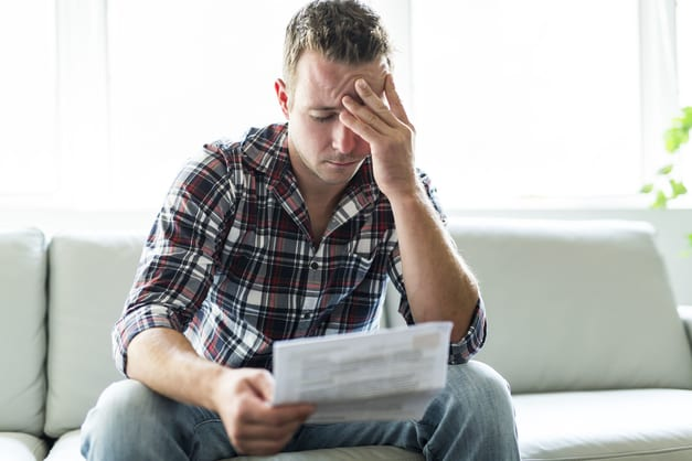 man looking frustrated at paper