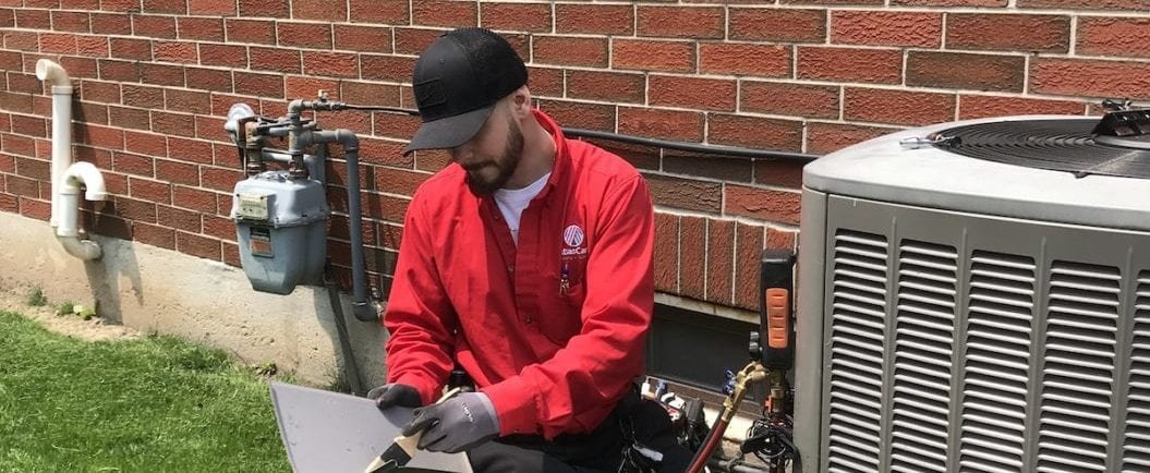 AtlasCare technician working on an air conditioner