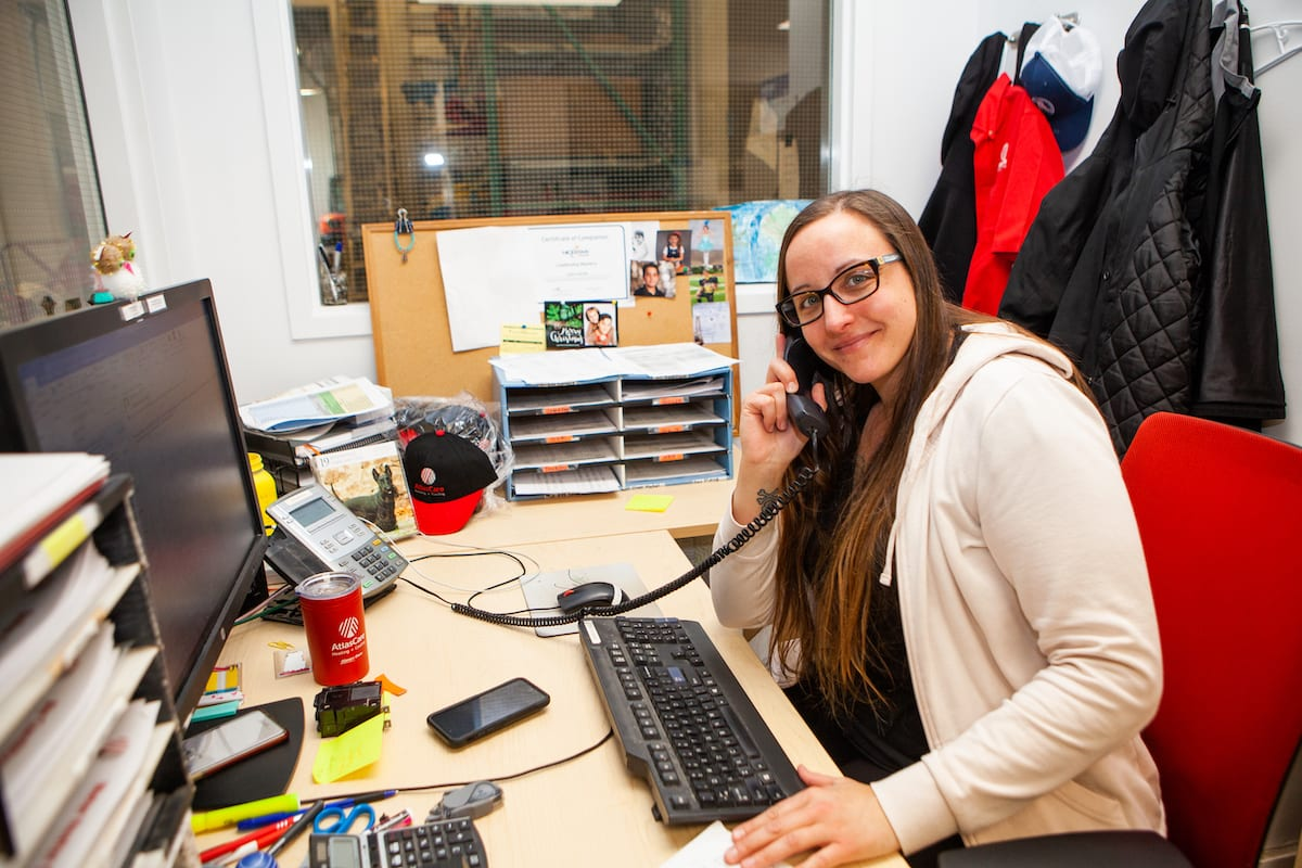 Photo of an AtlasCare employee on the phone at her desk