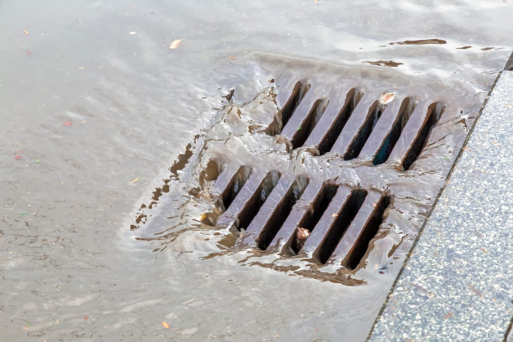 square grate sewer drain with water passing through it