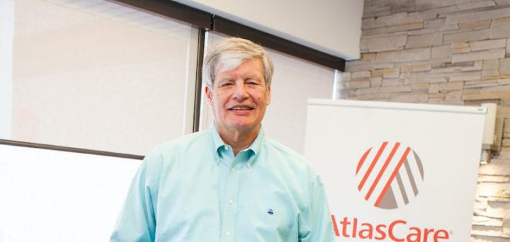 Photo of Roger Grochmal standing in front of an AtlasCare banner